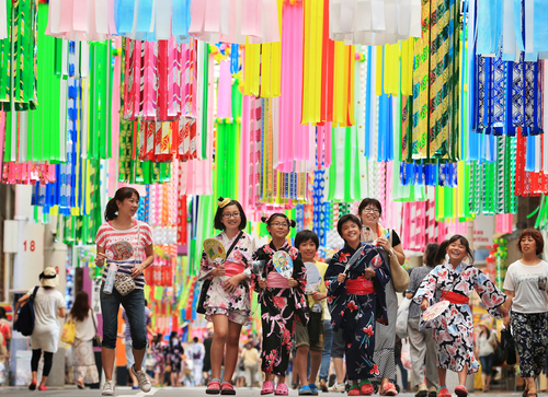 Entre o público, pessoas vestidas de yukata e famílias com crianças, aproveitando as férias de verão